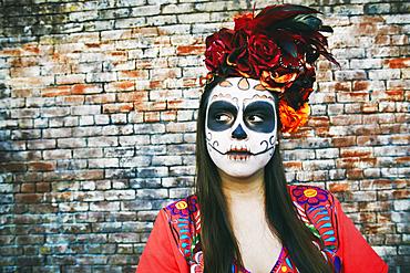Hispanic woman near brick wall wearing skull face paint