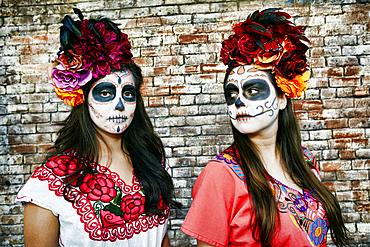 Women near brick wall wearing skull face paint