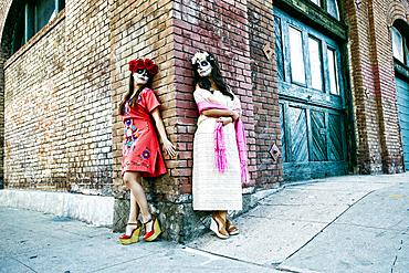 Women on sidewalk corner wearing skull face paint