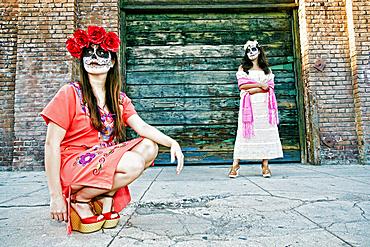 Women on sidewalk wearing skull face paint