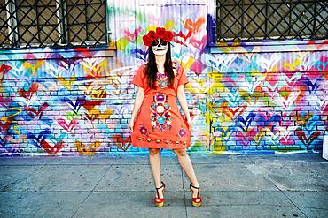 Hispanic woman standing on sidewalk wearing skull face paint