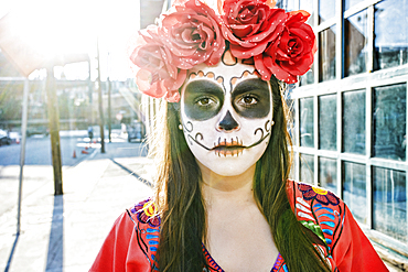Hispanic woman on sidewalk wearing skull face paint