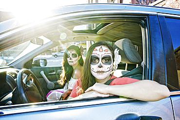 Women in car wearing skull face paint