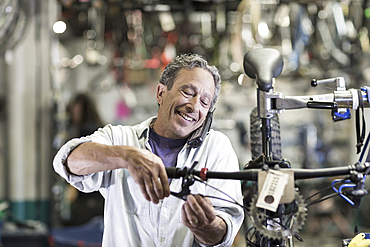 Caucasian man talking on telephone and repairing brakes on bicycle