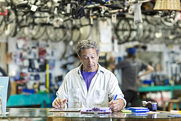 Caucasian man in bicycle shop writing on clipboard