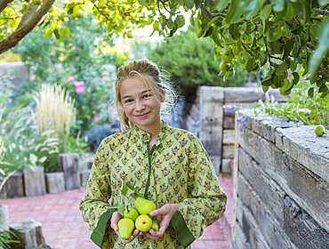 Portrait of smiling Caucasian girl holding pears