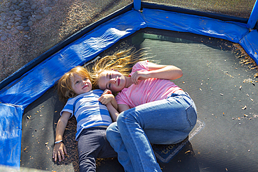 Caucasian brother and sister laying on trampoline