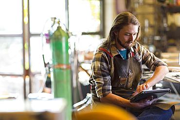 Caucasian man reading a digital tablet in workshop