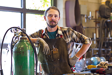 Confident Caucasian man leaning on gas tank in workshop