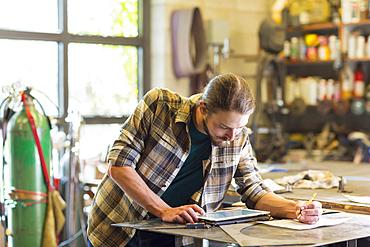 Caucasian man using digital tablet in workshop