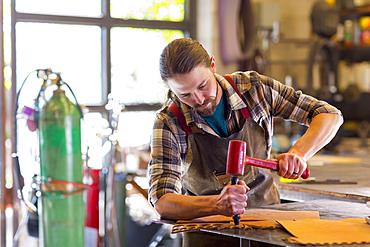 Caucasian man hammering leather