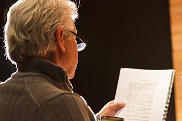 Hispanic man reading script in theater