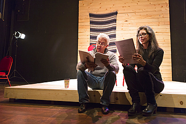 Hispanic man and woman reading scripts on theater stage