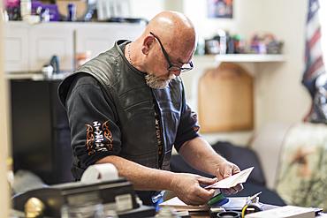 Caucasian man reading paperwork on clipboard