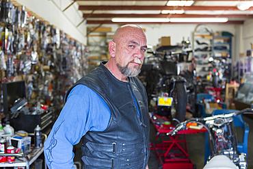 Portrait of Caucasian man repairing motorcycle