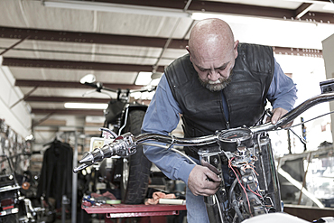 Caucasian man repairing motorcycle