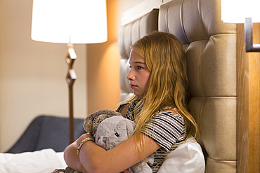 Frustrated Caucasian girl holding stuffed animals on hotel bed