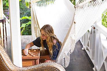 Caucasian girl sitting in hammock playing checkers