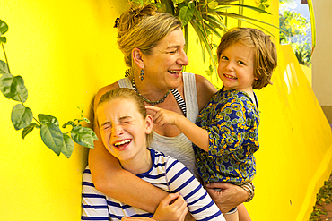 Laughing Caucasian mother hugging son and daughter
