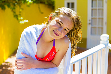 Wet Caucasian girl leaning on railing