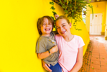 Caucasian girl leaning on yellow wall holding brother