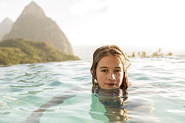 Caucasian girl swimming in infinity pool