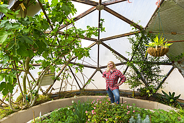 Caucasian woman posing in greenhouse