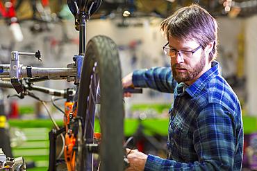 Caucasian man repairing bicycle in shop