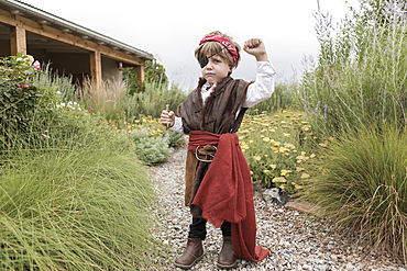 Caucasian boy wearing pirate costume holding knife