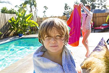 Caucasian boy wrapped in towel near swimming pool