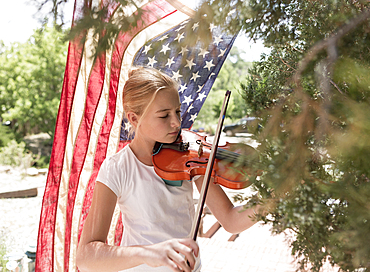 Caucasian girl playing violin near American flag