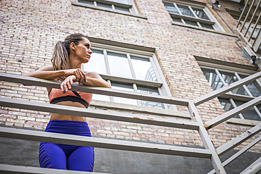 Caucasian woman leaning on urban railing