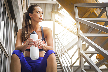 Caucasian woman sitting on urban staircase holding water bottle