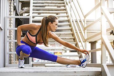 Caucasian woman stretching leg on urban staircase