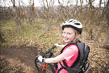 Caucasian girl riding bicycle on forest path