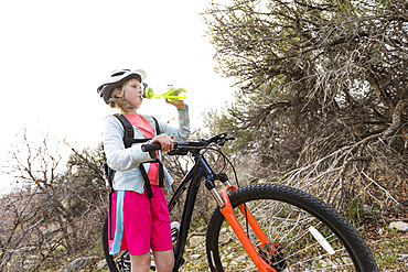 Caucasian girl holding bicycle and drinking water