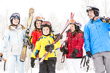 Smiling Caucasian family carrying skis in snow