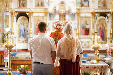Couple and priest standing in church