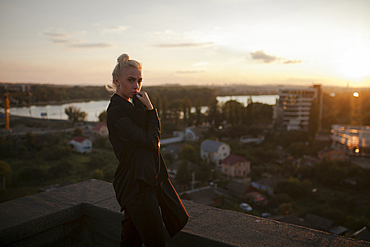 Pensive Caucasian woman standing on roof at sunset