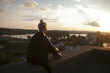 Caucasian woman on roof admiring scenic view of sunset
