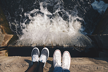 Feet of people standing at the edge of flowing water
