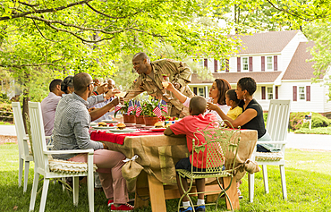 Multi-generation family toasting with lemonade at picnic