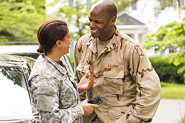 Smiling African American soldier couple talking near car