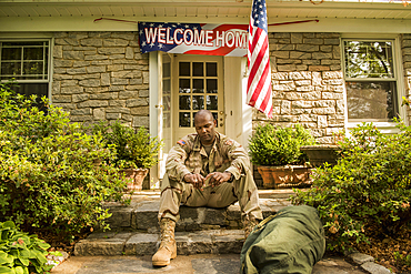 Frustrated African American soldier sitting on front stoop