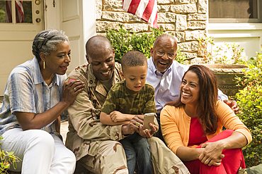 Soldier and multi-generation family looking down at cell phone