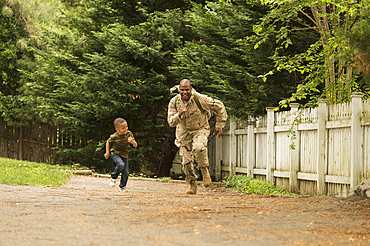 African American soldier running in race with son