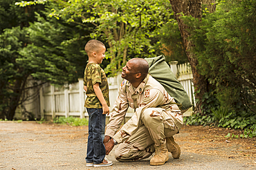 African American soldier tying shoelace for son