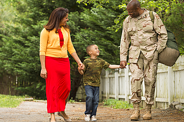 African American woman and boy walking with soldier
