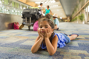 Bored girl laying on floor of airport