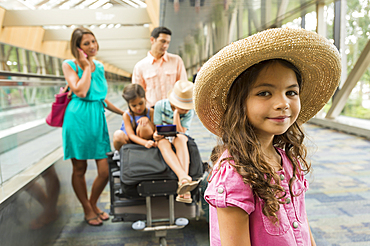 Portrait of girl waiting in airport with family